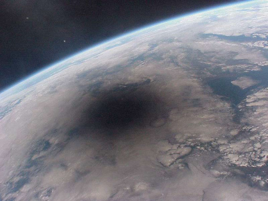Here is what the Earth looks like during a solar eclipse. The shadow of the Moon can be seen darkening part of Earth. This shadow moved across the Earth at nearly 2000 kilometers per hour. Credit: Mir 27 Crew; Copyright: CNES